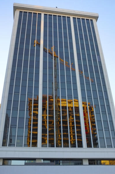 In this Saturday, Jan. 19, 2013 photo, construction is reflected in an existing office building in Arlington, Va. The Commerce Department says construction spending in the U.S. fell 2.1 percent in January compared with December, the largest drop in 18 months. (AP Photo/J. David Ake)