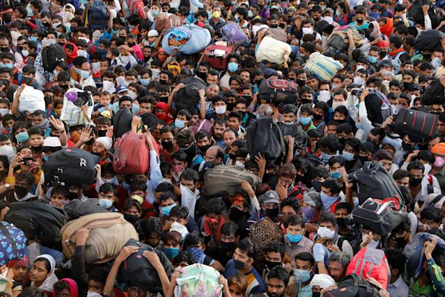 Migrant workers crowd up outside a bus station as they wait to board buses to return to their villages during a 21-day nationwide lockdown to limit the spreading of coronavirus disease (COVID-19), in Ghaziabad, on the outskirts of New Delhi, India March 28, 2020. REUTERS/Anushree Fadnavis