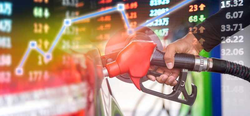 A hand holding a fuel nozzle with a market data chart in the background.