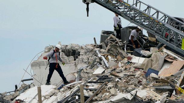PHOTO: Rescue worker walk among the rubble where a wing of a 12-story beachfront condo building collapsed, June 24, 2021, Surfside, Fla. (Lynne Sladky/AP)