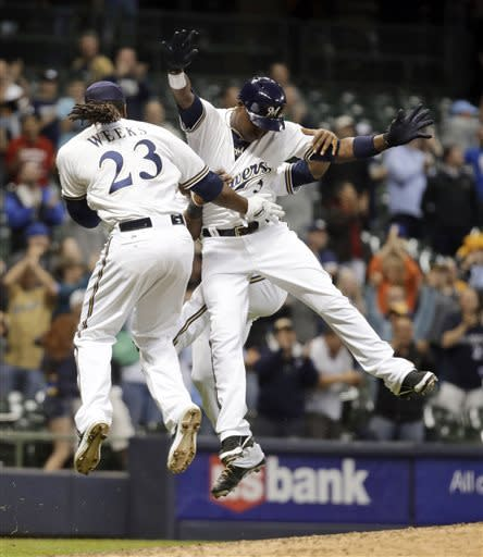 Milwaukee Brewers' Yuniesky Betancourt (3) celebrates with Rickie Weeks (23) and Jean Segura after hitting in the game-winning run during the 10th inning of a baseball game against the Oakland Athletics Tuesday, June 4, 2013, in Milwaukee. The Brewers won 4-3. (AP Photo/Morry Gash)