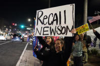 FILE — In this Nov. 21, 2020 file photo demonstrators shout slogans while carrying a sign calling for a recall on Gov. Gavin Newsom during a protest against a stay-at-home order amid the COVID-19 pandemic in Huntington Beach, Calif. Newsom is facing the second recall of a governor in California history. His response to the coronavirus has been a dominating force in the race. (AP Photo/Marcio Jose Sanchez, File)