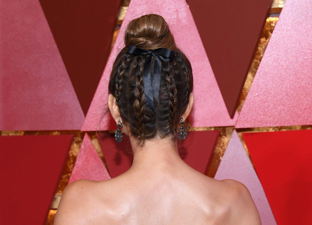<p>Maria Menounos added four French braids up the back of her updo, each of them making their way to her high topknot. A black ribbon adds a finishing touch.</p>