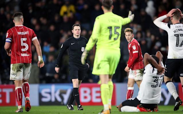 "It was a decade ago this year when Derby County slipped out of the Premier League amid acute embarrassment and a record low points total. And Derby's hopes of ending that painful exile were damaged on Friday night by a bewildering refereeing decision which left manager Gary Rowett frustrated. After his emerging team were denied by not one, but two Bristol City goalkeepers, referee Darren England took centre stage three minutes from time by booking Cameron Jerome for simulation. Jerome, a Derby substitute, was clearly fouled by City defender Aden Flint in the penalty area yet was punished for diving to complete an excruciating evening for Rowett's promotion chasers. Frank Fielding prevented Derby from taking the lead in the first half before a groin injury ensured he was replaced by Luke Steele for the second period, with City's other goalkeeper helping end a run of five successive defeats for his team with two fine saves. But it was the contentious incident in the 87th minute which riled Rowett, though his team remain in second place. Cameron Jerome goes down in the box Credit: AKY SPORTS ""It was a stonewall penalty,"" he said. ""It's the most obvious spot-kick you'll see and I've seen it three or four times. ""When it's a game that tight, one thing can define the game. The referee didn't give it, that's what it is. He didn't do it on purpose but reality is that's cost us. ""I am disappointed and I spoke to the referee afterwards. If you showed it 1,000 people, 1,000 would say it was a penalty."" Derby arguably should have secured their ninth win from the last 12 Championship games long before the pivotal moment. Matej Vydra, their leading scorer, forced a fine save from Fielding after a low free-kick from 25 yards and then from the corner Curtis Davies had a header cleared off the line by Flint. Ten minutes before half-time, Jonny Russell struck the crossbar from a set-piece. Lee Johnson, the City manager, was forced into a tactical reshuffle at half-time, bringing on record signing Famara Diédhiou for his first game since October while Fielding, the goalkeeper, was also replaced due to injury. Fielding's deputy, Steele, produced an excellent save in the 63rd minute to push Tom Lawrence's fierce shot over the bar. Steele then frustrated Vydra from close range with another instinctive stop as the City defence were caught out by David Nugent's clever pass. Rowett introduced Jerome for the final 14 minutes and it was Derby's new £1.5 million signing who provided the late controversy when he collapsed under Flint's challenge. Johnson said: ""It did look like a penalty but sometimes you get away with those. My initial reaction was that it's a dive but I'd be upset if one of my players was booked for that. ""You could say we were lucky to get away with a point but we worked very hard. It's a good point for us and it stops the mini rot."" Team details Derby County (4-2-3-1) Carson; Wisdom, Keogh, Davies, Forsyth; Thorne, Huddlestone; Russell, Vydra (Jerome 76), Lawrence (Weimann 76); Nugent (Winnall 76). Subs Mitchell (g), Baird, Pearce, Hanson. Booked Jerome. Bristol City (4-4-2) Fielding (Steele 46); Wright, Flint, Baker (Diedhiou 46), Magnusson; Brownhill, Pack, Smith, Bryan; Paterson, Reid. Subs Kelly, Eliasson, Walsh, Kent, Engvall. Booked Bryan. Referee Darren England (South Yorkshire)."