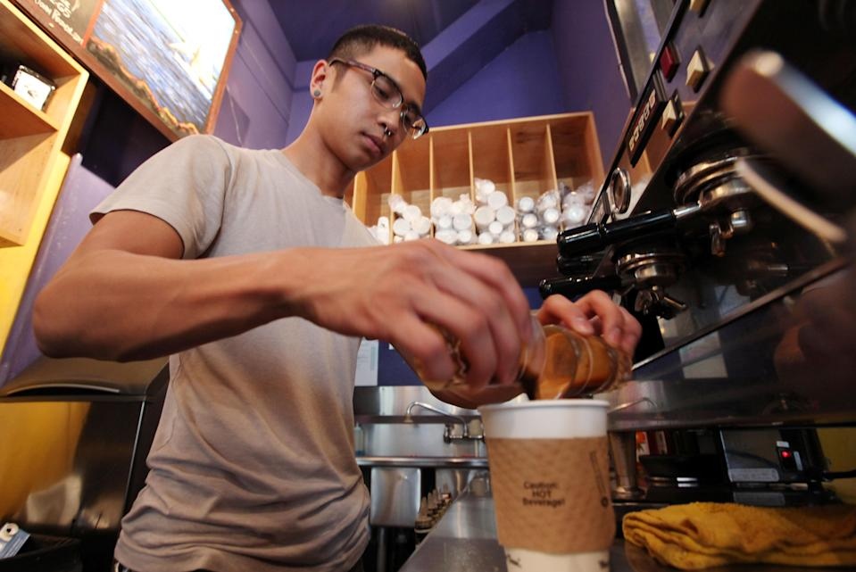 In this photo taken Thursday, April 19, 2012, barista Michael Bledsoe prepares a two-shot coffee drink in a coffee shop in Seattle. The college class of 2012 is in for a rude welcome to the world of work. A weak labor market already has left half of young college grads either jobless or underemployed in positions that don't fully use their skills and knowledge. (AP Photo/Elaine Thompson)