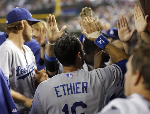 Los Angeles Dodgers' Andre Either is greeted by teammates after scoring on a ground out by teammate Skip Schumaker during the fourth inning of a baseball game against the Arizona Diamondbacks, Tuesday, July 9, 2013, in Phoenix. (AP Photo/Matt York)