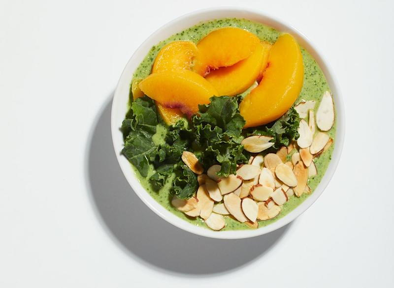 peaches and green kale smoothie bowl on white background