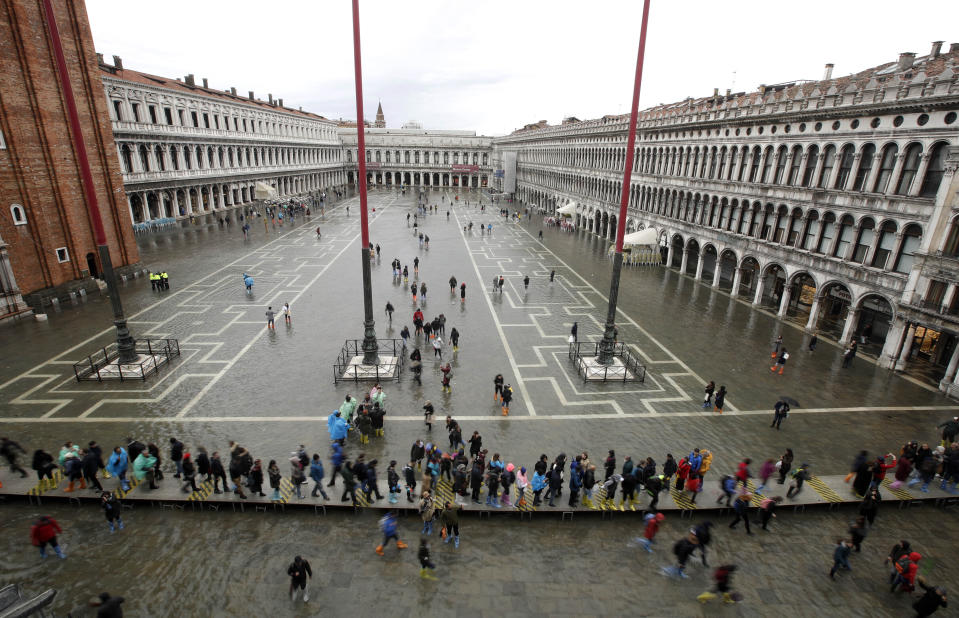 People walk in a flooded St. Mark's Square in Venice, Italy, Tuesday, Nov. 12, 2019. (Photo: Luca Bruno/AP)