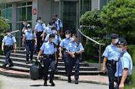 Police officers leave the Apple Daily newspaper offices in Hong Kong