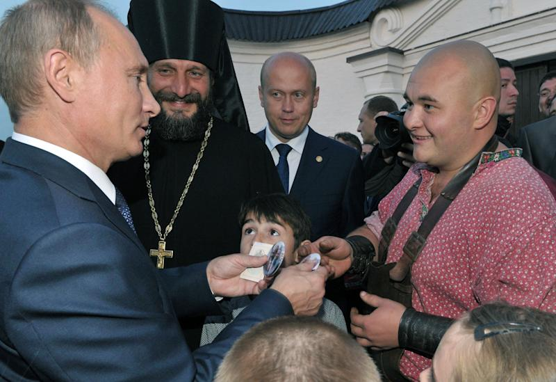 Russian President Vladimir Putin, left, visits a historical and architectural museum in Bolgar, about 700 kilometers (450 miles) east of Moscow, central Russia, Tuesday, Aug. 28, 2012. Second left is Father Superior Siluan. (AP Photo/RIA-Novosti, Alexei Nikolsky, Presidential Press Service)