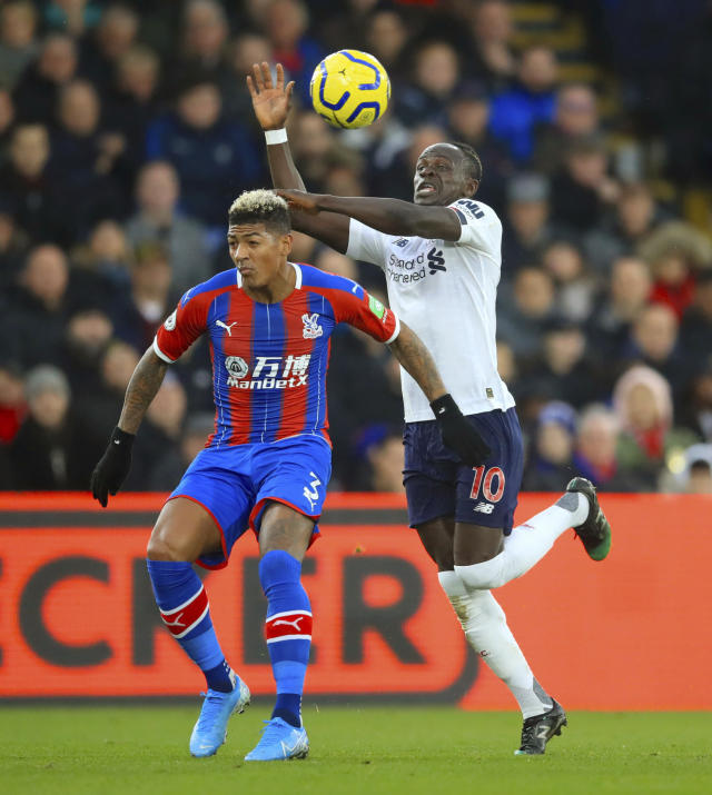 Crystal Palace's Patrick van Aanholt, left and Liverpool's Sadio Mane battle for the ball during the English Premier League soccer match between Crystal Palace and Liverpool, at Selhurst Park, London, Saturday, Nov. 23, 2019. (Adam Davy/PA via AP)