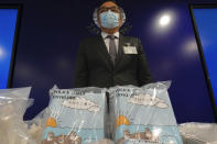 Li Kwai-wah, senior superintendent of Police National Security Department, poses in front of evidence including three children's books on stories that revolve around a village of sheep which has to deal with wolves from a different village, before a press conference in Hong Kong Thursday, July 22, 2021. Hong Kong's national security police on Thursday arrested five people from a trade union of the General Association of Hong Kong Speech Therapists on suspicion of conspiring to publish and distribute seditious material, in the latest arrests made amid a crackdown on dissent in the city. (AP Photo/Vincent Yu)