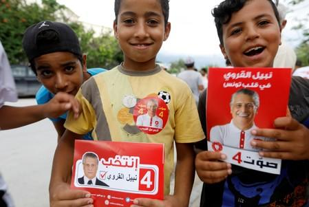 Boys hold flyers of presidential candidate Nabil Karoui during a campaign in Tunis
