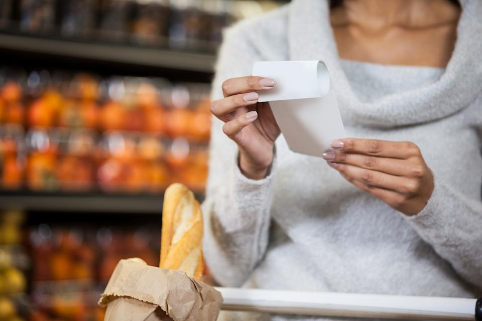 Mid section of woman holding bill in grocery section of supermarket