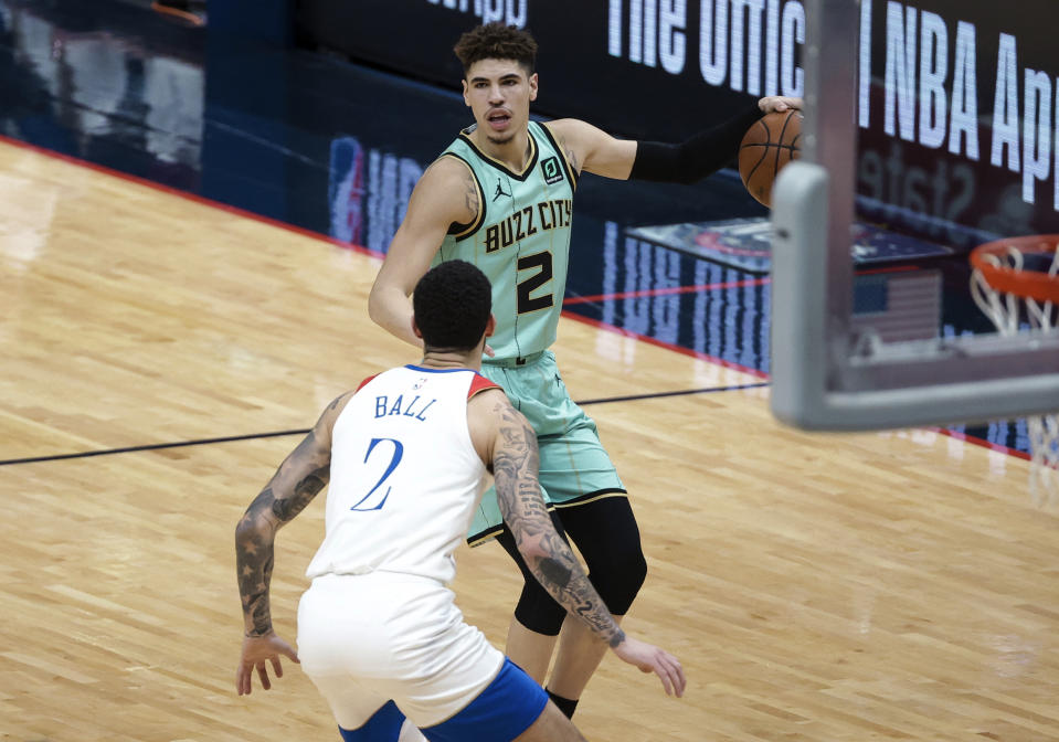 Charlotte Hornets guard LaMelo Ball, rear, is defended by New Orleans Pelicans guard Lonzo Ball during the first quarter of an NBA basketball game in New Orleans, Friday, Jan. 8, 2021. (AP Photo/Derick Hingle)