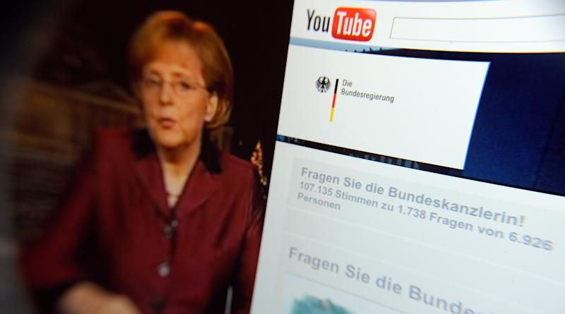 FILE- This Dec.31, 2008 file photo taken through a magnifying glass shows a video of German Chancellor Angela Merkel  delivering her New Year's speech beside the Youtube channel of the German government. YouTube announced Monday, Oct. 8, 2012, that it is  extending its original programming initiative into Europe, with at least 60 new video channels from media companies including Britain's BBC, London-based FreemantleMedia and the Netherlands' Endemol. The Google Inc.-owned video site said Monday it is launching more than 60 new video channels with content from Britain, Germany, France, and the United States. (AP Photo/dapd, David Hecker, File)