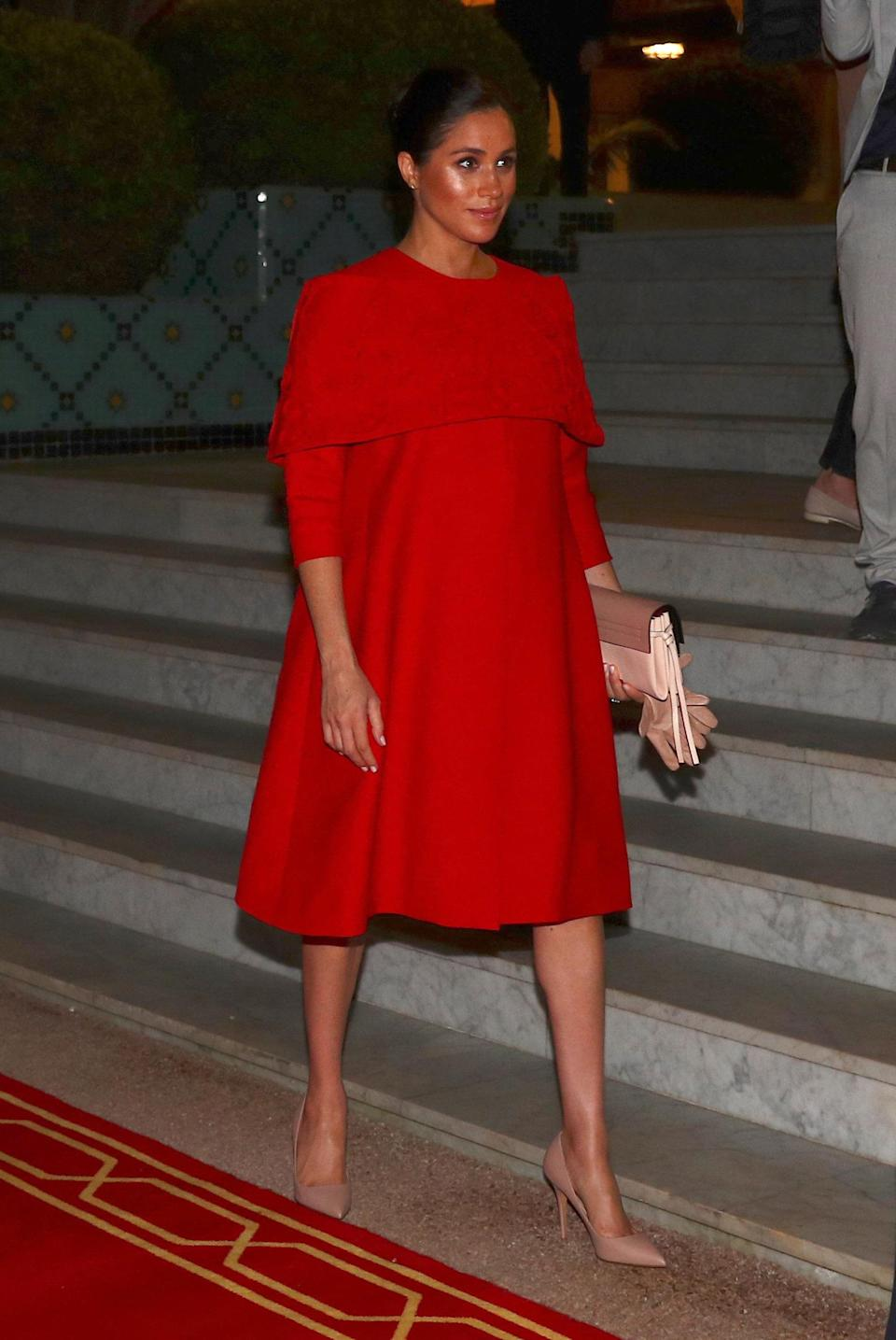 """<p>The Duke and Duchess of Sussex arrived in Casablanca, Morocco on Saturday evening. Meghan paid tribute to the country's flag with her red caped Valentino dress and the brand's <a rel=""""nofollow noopener"""" href=""""https://www.valentino.com/en-gb/cross-body-bags_cod272216333676817.html#dept="""" target=""""_blank"""" data-ylk=""""slk:small v-ring crossbody bag."""" class=""""link rapid-noclick-resp"""">small v-ring crossbody bag.</a> Nude pumps completed her arrival look. [Photo: PA] </p>"""