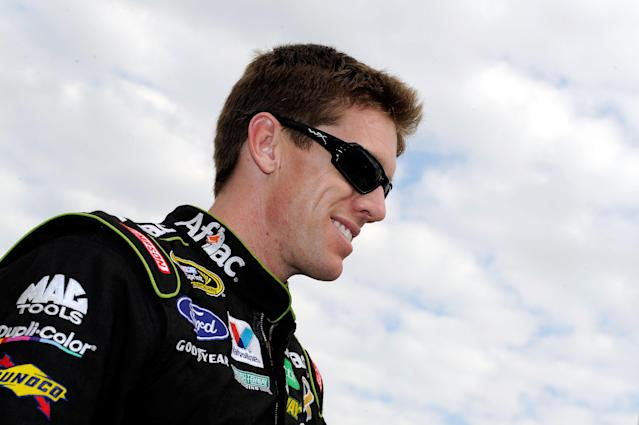 FORT WORTH, TX - NOVEMBER 06: Carl Edwards, driver of the #99 Aflac Ford, smiles as he stands on the grid prior to the start of the NASCAR Sprint Cup Series AAA Texas 500 at Texas Motor Speedway on November 6, 2011 in Fort Worth, Texas. (Photo by John Harrelson/Getty Images for NASCAR)