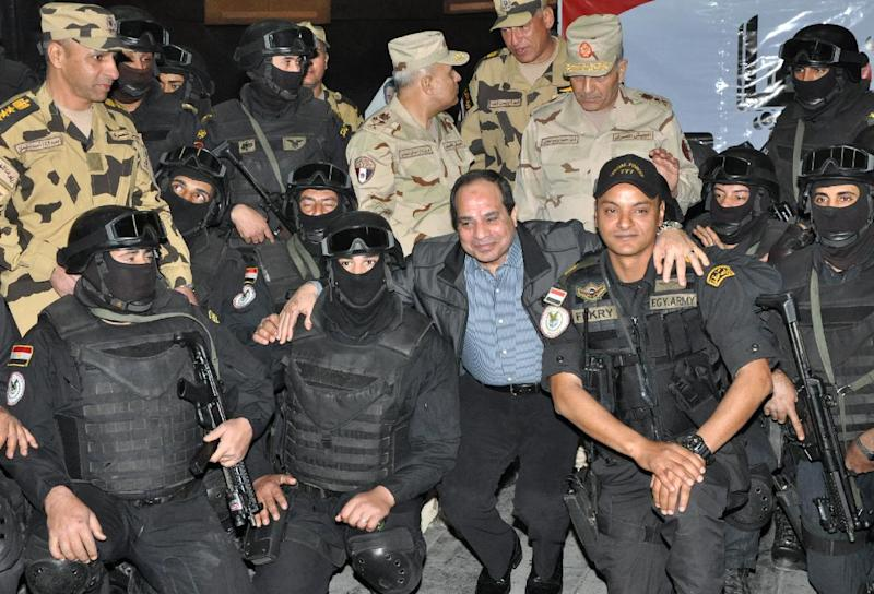 Egyptian President Abdel Fattah al-Sisi poses on February 3, 2015 with members of an Armed Forces Unit during a surprise visit to their base in the port city of Ismailia, east of Cairo (AFP Photo/)