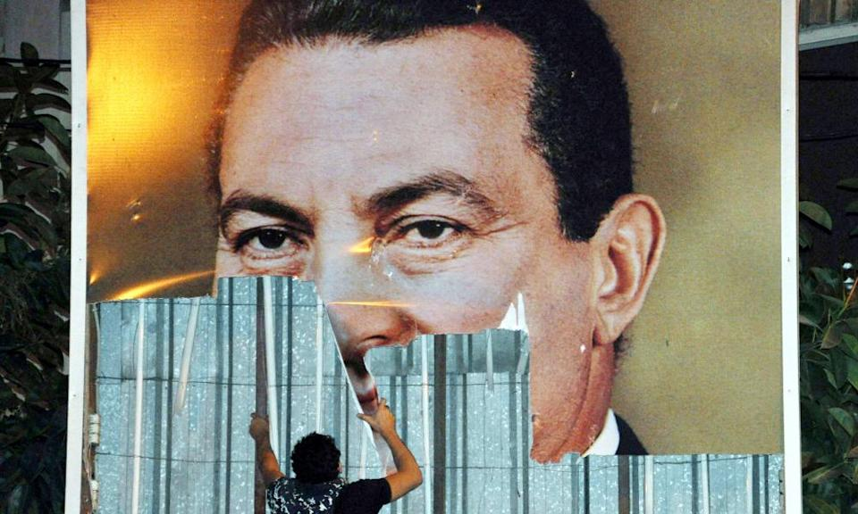 A protesters tearing down a poster of President Hosni Mubarak during a protest in Alexandria on 25 January 2011.