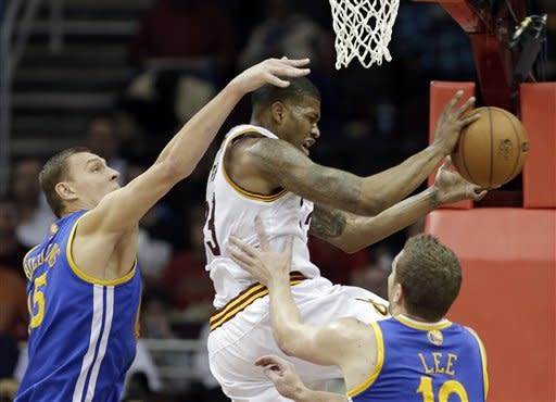 Golden State Warriors' Andris Biedrins, left, fouls Cleveland Cavaliers' Alonzo Gee during the first quarter of an NBA basketball game Tuesday, Jan. 29, 2013, in Cleveland. (AP Photo/Mark Duncan)