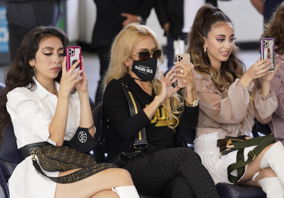 Cristy Solis, wife of singer Marco Antonio Solis, center, and their daughters Alison Solis, left, and Marla Solis take photos as they attend a press conference for Mexican grupera band Los Bukis at SoFi Stadium on Monday, June 14, 2021, in Inglewood, Calif. Twenty five years after their last show as a band, Los Bukis announced that they are reuniting for a U.S. tour. (AP Photo/Chris Pizzello)