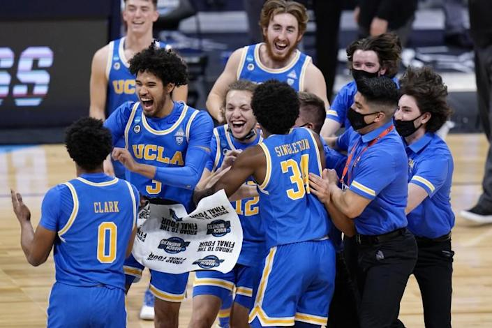 UCLA players celebrate after beating Alabama 88-78 in overtime of a Sweet 16 game in the NCAA.