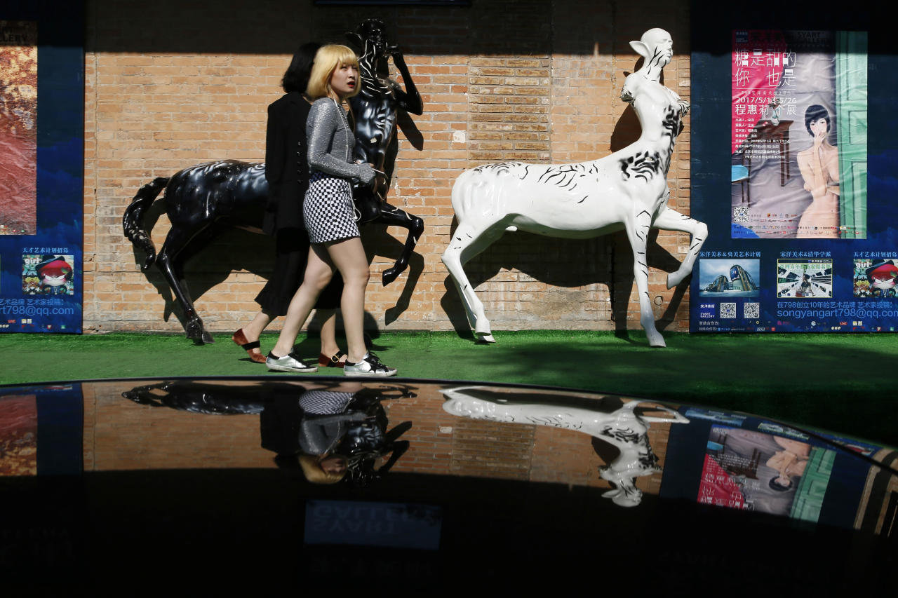 Visitors to the 798 art district walk past art installations outside a gallery in Beijing Tuesday, May 23, 2017. Started as a artist commune, the area quickly became popular with tourists and locals seeking a break from the more traditional sights in the Chinese capital. (AP Photo/Ng Han Guan)