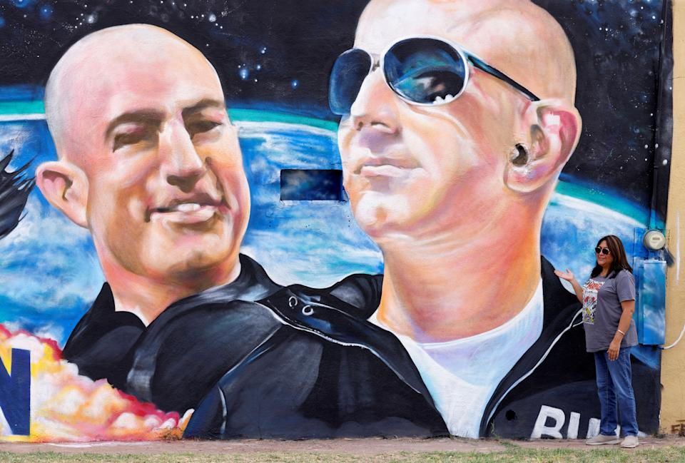 Margarita Moilina of El Paso, TX, poses next to a mural depicting billionaire American businessman Jeff Bezos (C) and his brother Mark (L) one day before their launch on Blue Origin's inaugural flight to the edge of space, in the nearby town of Van Horn, Texas, U.S. July 19, 2021.   REUTERS/Joe Skipper