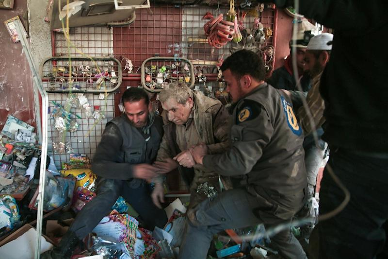 In this file photo taken on March 25, 2017, White Helmets volunteers rescue a survivor following reported air-strikes on the rebel-held town of Hammuriyeh (AFP Photo/Msallam ABDALBASET)