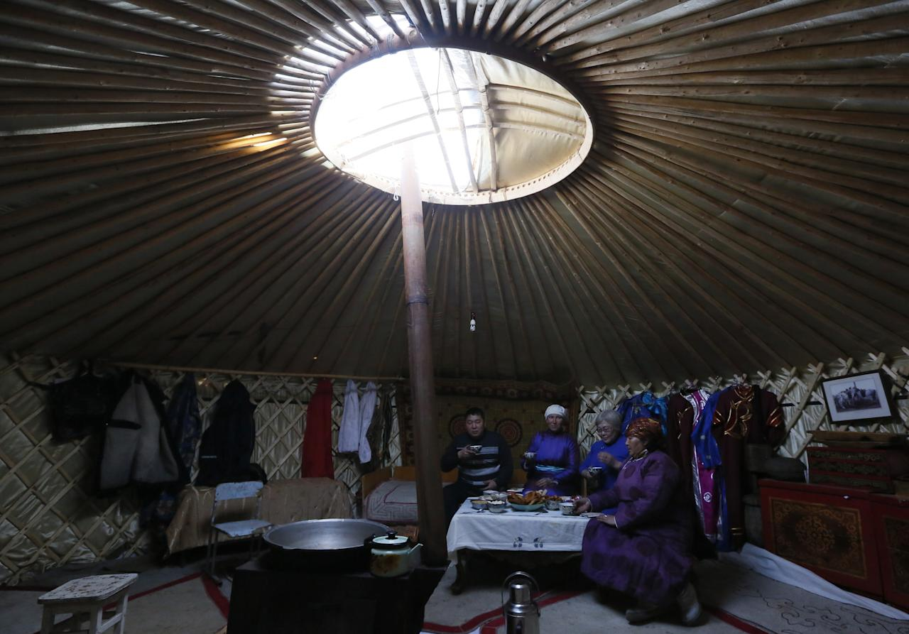 <p>Tanzurun Darisyu, right, head of a Tuvan private farm located in the Kara-Charyaa area, has a meal with her neighbours and relatives inside a yurt south of Kyzyl town, the administrative center of the Republic of Tuva (Tyva region) in southern Siberia, Russia, on Feb. 14, 2018. (Photo: Ilya Naymushin/Reuters) </p>