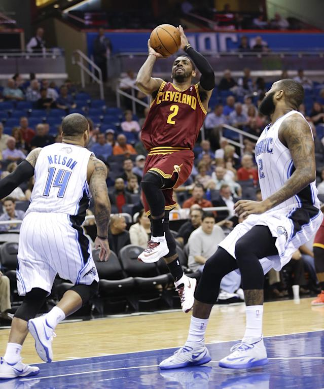 Cleveland Cavaliers' Kyrie Irving (2) makes a shot as he gets between Orlando Magic's Jameer Nelson (14) and Kyle O'Quinn, right, during the first half of an NBA basketball game in Orlando, Fla., Wednesday, April 2, 2014. (AP Photo/John Raoux)