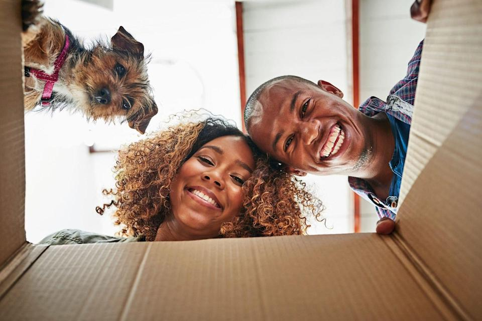couple and their dog looking a box that arrived with their dog subscription