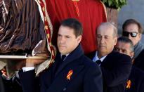 Relatives Luis Alfonso de Borbón, left, Francis Franco, center, and Jaime Martínez-Bordiú, right, carry the coffin with the remains of Spanish dictator General Francisco Franco at the Valley of the Fallen mausoleum near El Escorial, outskirts of Madrid, Spain, Thursday, Oct. 24, 2019. Spain is exhuming the remains of Spanish dictator Gen. Francisco Franco from his grandiose mausoleum outside Madrid so he can be reburied in a small family crypt north of the capital. (AP Photo/Juan Carlos Hidalgo, Pool)