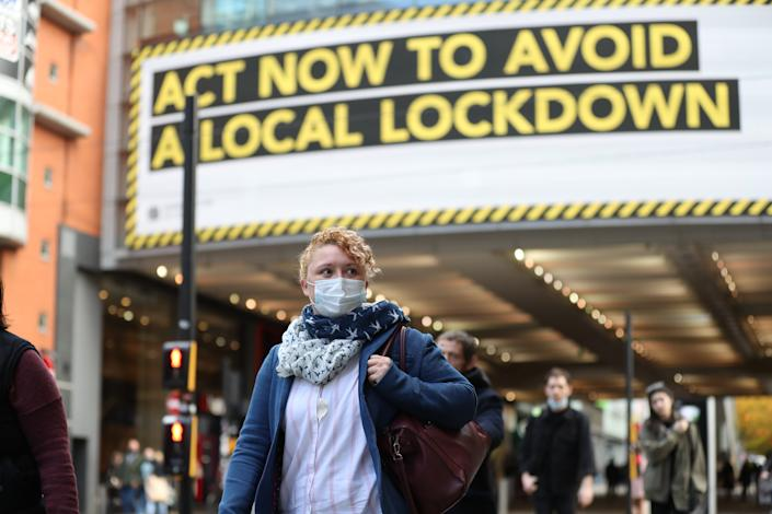 A woman wearing a face mask walks through Manchester. Greater Manchester will be placed under stricter coronavirus controls after last-ditch talks with the Prime Minister aimed at securing additional financial support concluded without an agreement. (Photo by Martin Rickett/PA Images via Getty Images)