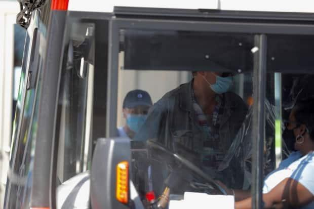 OC Transpo riders get on board a bus last summer during the COVID-19 pandemic. There has been a surge in COVID-19 cases amongst employees, prompting the union to call for better measures to protect operators and maintenance workers.