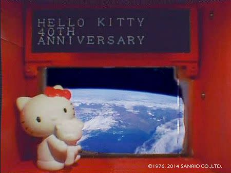 A 4-cm (1.6-inch) tall Hello Kitty figurine placed under a scrolling display in front of a window of the Hodoyoshi-3 satellite, is seen in what Sanrio Co. said is a still image from a video, made available to Reuters on August 14, 2014. REUTERS/Sanrio Co. ,Ltd./Handout via Reuters