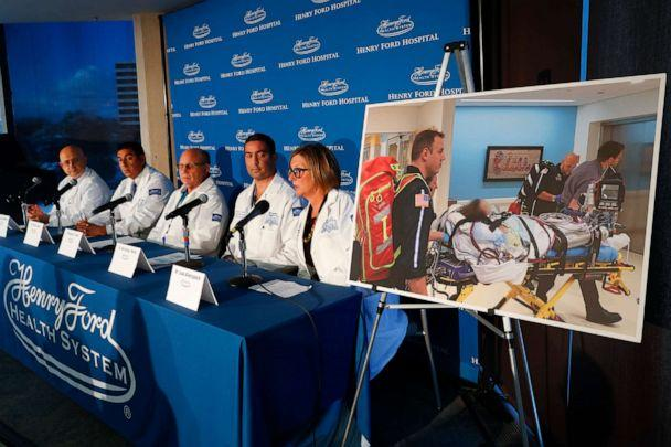 PHOTO: A photo of a patient being transported is displayed while medical staff at Henry Ford Hospital answer questions during a news conference in Detroit, Nov. 12, 2019. (Paul Sancya/AP)