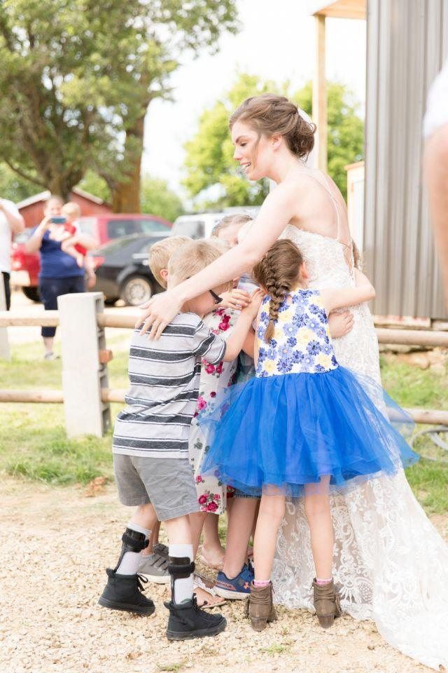 The bride in her dress is surrounded by little students.