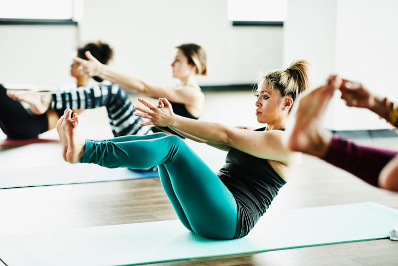 Women in boat pose during hot yoga class in exercise studio