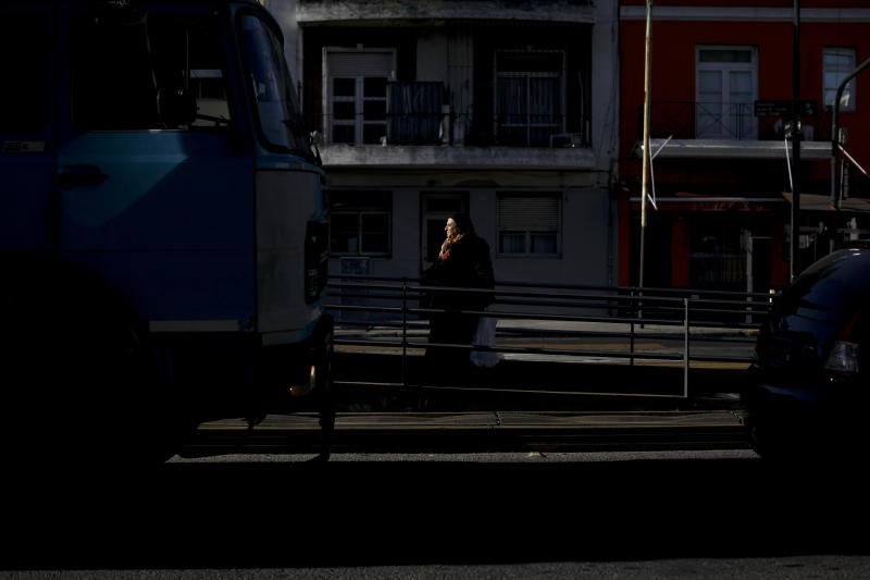 A woman waits for the bus in Buenos Aires, Argentina, Tuesday, Aug. 13, 2019. Increasing hardship has been evident for some time in Argentina. Many struggle to pay utility bills. Families living on the streets outside shopping malls, bus stations and parks have become an increasingly common sight in Buenos Aires. (AP Photo/Natacha Pisarenko)