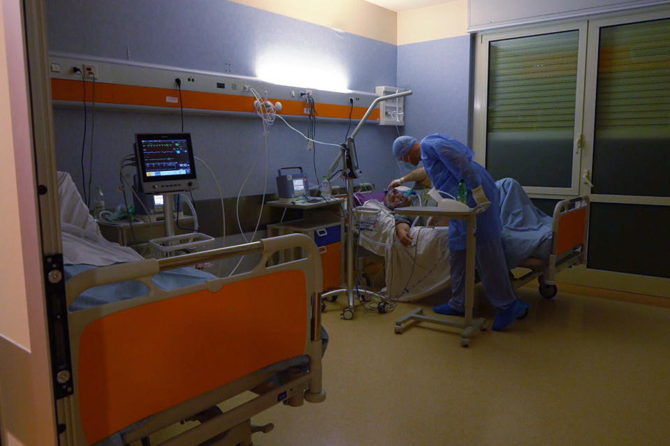 Dr. Paolo Petrassi, the night shift coordinator at Casalpalocco Covid 3 hospital in the outskirts of Rome, checks one of the patients during the new year night, Friday, Jan. 1, 2021. At the Casalpalocco Covid 3 Hospital doctors and nurses barely seemed to register the new year as they tended to 100 patients struggling with serious to critical illness as a result of coronavirus infections. (AP Photo/Andrea Rosa)