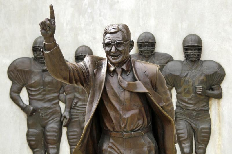 FILE - The statue of former Penn State University head football coach Joe Paterno stands outside Beaver Stadium in State College, Pa., in this July 13, 2012 file photo. Police and construction workers have barricaded both sides of street and the sidewalks near the Joe Paterno statue at Penn State University Sunday July 22, 2012. A chain-link fence has been erected around the perimeter surrounding the statue.(AP Photo/Gene J. Puskar, File)