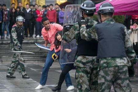 Police and civilians take part in an anti-terrorism drill at a college in Hangzhou, Zhejiang province, China