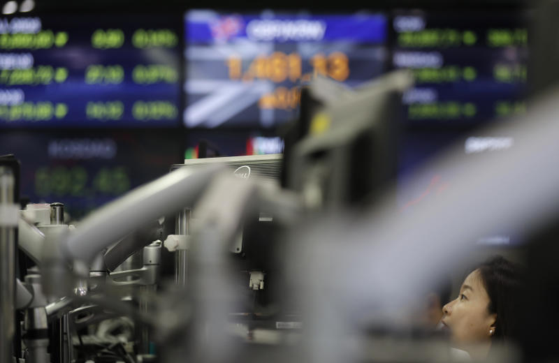 A currency trader watches computer monitors at the foreign exchange dealing room in Seoul, South Korea, Tuesday, Aug. 13, 2019. Asian stock markets followed Wall Street lower Tuesday amid anxiety the U.S.-Chinese trade war will hurt already slowing global economic growth. (AP Photo/Lee Jin-man)