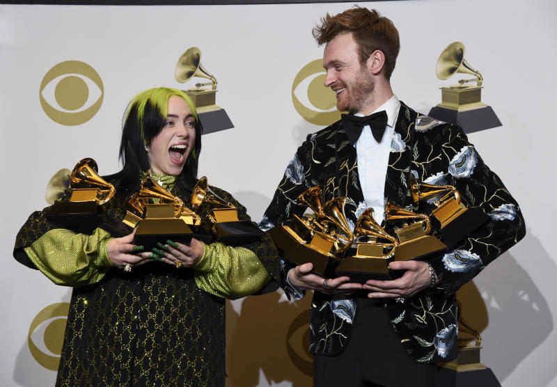 "Billie Eilish, left, and Finneas O'Connell pose in the press room with the awards for best album, best engineered album and best pop vocal album for ""We All Fall Asleep, Where Do We Go?,"" best song and record for ""Bad Guy,"" best new artist and best producer, non-classical at the 62nd annual Grammy Awards at the Staples Center on Sunday, Jan. 26, 2020, in Los Angeles. (AP Photo/Chris Pizzello)"