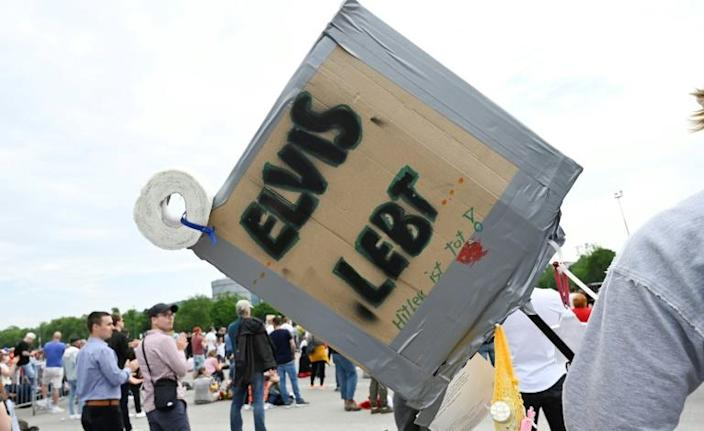 A demonstrator holds a placard that reads 'Elvis is alive' at a protest in Stuttgart (AFP Photo/THOMAS KIENZLE)
