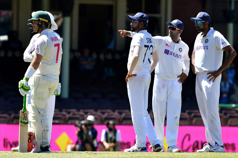 India's Mohammed Siraj (C) stands along with his teammates as Australia's captain Tim Paine (L) watches as the game was halted after allegedly some remarks were made by the spectators on the fourth day of the third cricket Test match between Australia and India at the Sydney Cricket Ground (SCG) in Sydney on January 10, 2021. (Photo by SAEED KHAN/AFP via Getty Images)