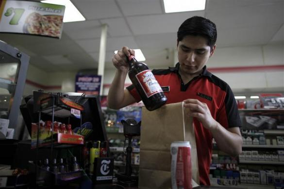 Abel Santiago, 21, serves a customer at a 7-Eleven convenience store in Santa Monica, California, April 24, 2012. Santiago studied for one year at Universidad Anahuac Oaxaca for a degree in law. He has worked at the store for five months and hopes to return to Mexico to finish his degree.