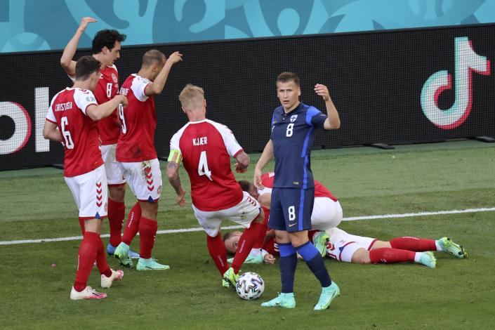 Denmark's players go to his teammate Christian Eriksen after he collapsed during the Euro 2020 soccer championship group B match between Denmark and Finland at Parken stadium in Copenhagen, Denmark, Saturday, June 12, 2021. (Wolfgang Rattay/Pool via AP)